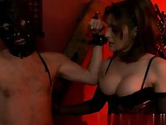 Handsome babe wearing a sex-positive harness and sexually abusing her slave