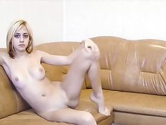 Tempting blonde honey is posing on the couch showing her superb body