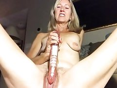 Kinky looking mature lady is filling up her vagina with a massive dildo